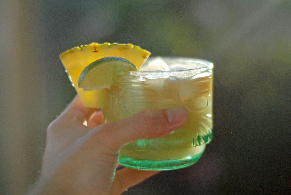 hand holding a trader vics mai tai in a tiki glass