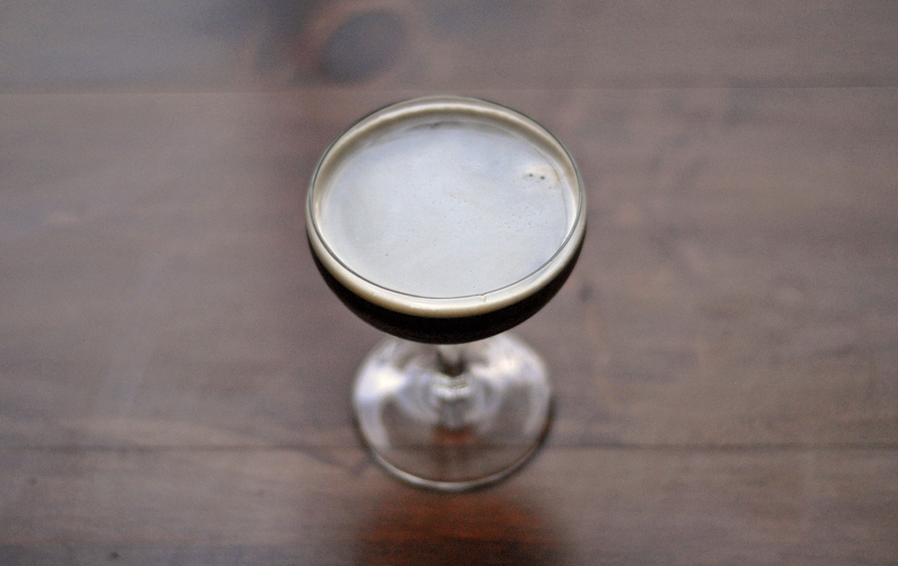 coupe-glass-of-Last-Call-to-Porter-cocktail-shot-from-above-on-wood-table.png