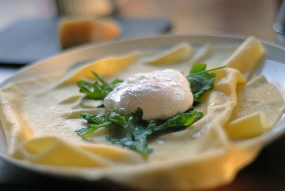 poached-egg-resting-in-blanches-arugula-on-a-sheet-of-fresh-pasta.png
