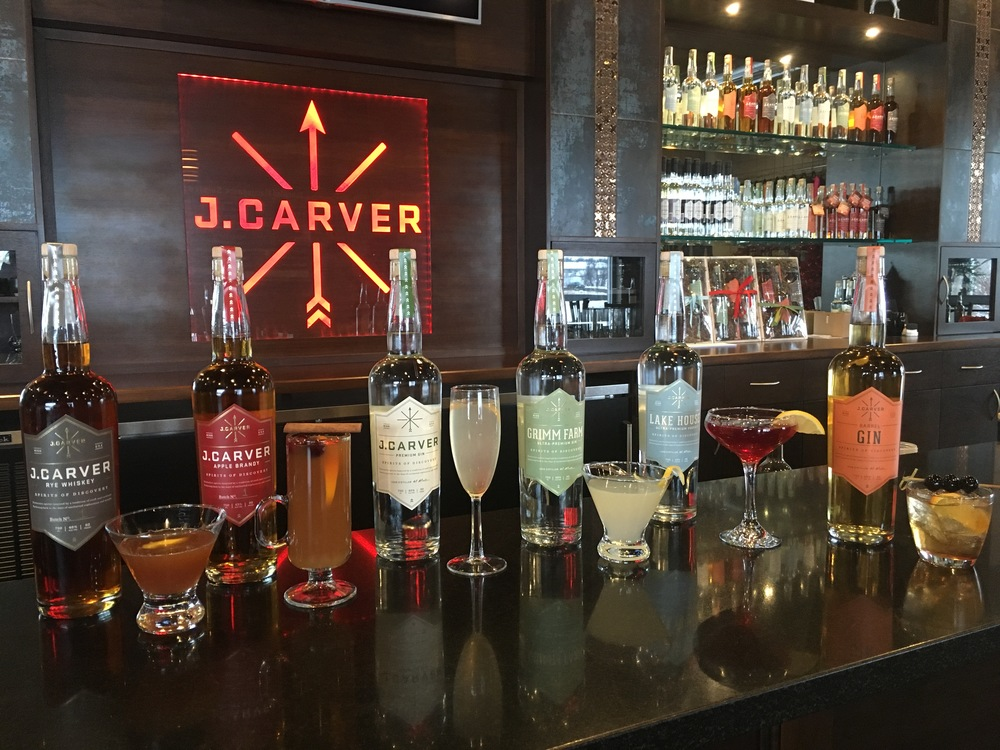 A line up of J. Carver Specialty cocktails: J. Carver Rye Frisco, Mulled Cider and Apple Brandy, a spin on a  J. Carver French 75, Grimm Farm Bees Knees, Lake House Cosmo, and the J. Carver Barrel Gin Old Fashioned