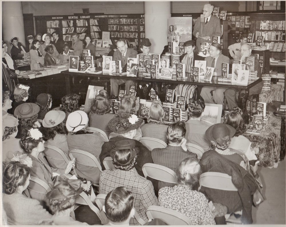 An autograph party featuring the writers of the anthology  Chicago Murder . The event took place in June 1945 at the book department of Marshall Field & Co. in downtown Chicago. Look at that packed house! Every seat is full and there is standing room only. They're going to need all those stacks of  Chicago Murder !