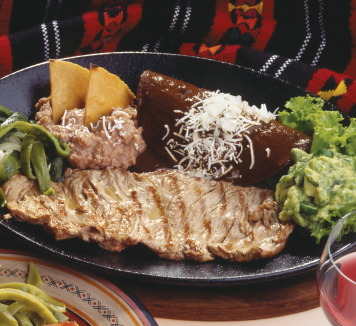 The Carne asada is a traditional plate from Tampico, served with grilled steak, two enchiladas, Mexican rice, refried beans with cheese and corn chips, square of feta cheese, mix salad, pico de gallo and guacamole.
