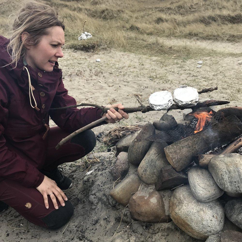 Vi har ikke grillrist med på turen, men Ragnhild har et godt tips; legg to pinner i kryss så de danner en v form og du har et bra redskap.