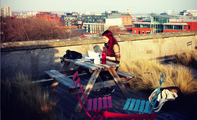 Charlotte (Design Assistant) working on the rooftop