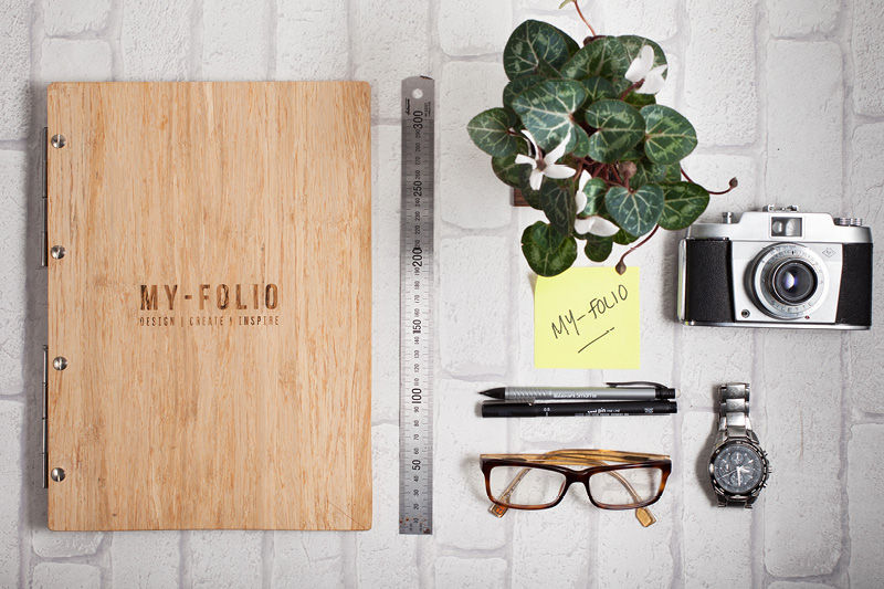 Bamboo portfolio in A4 portrait with logo engraving next to a camera, glasses and artists pens