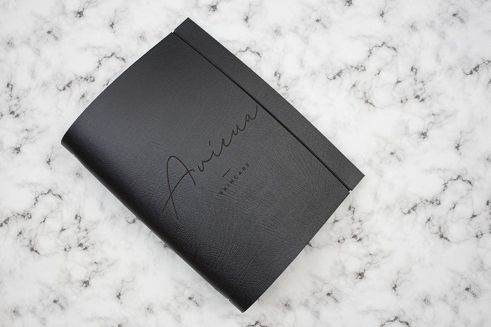 custom logo engraved bespoke leather A4 portrait ring binder portfolio on a marble background