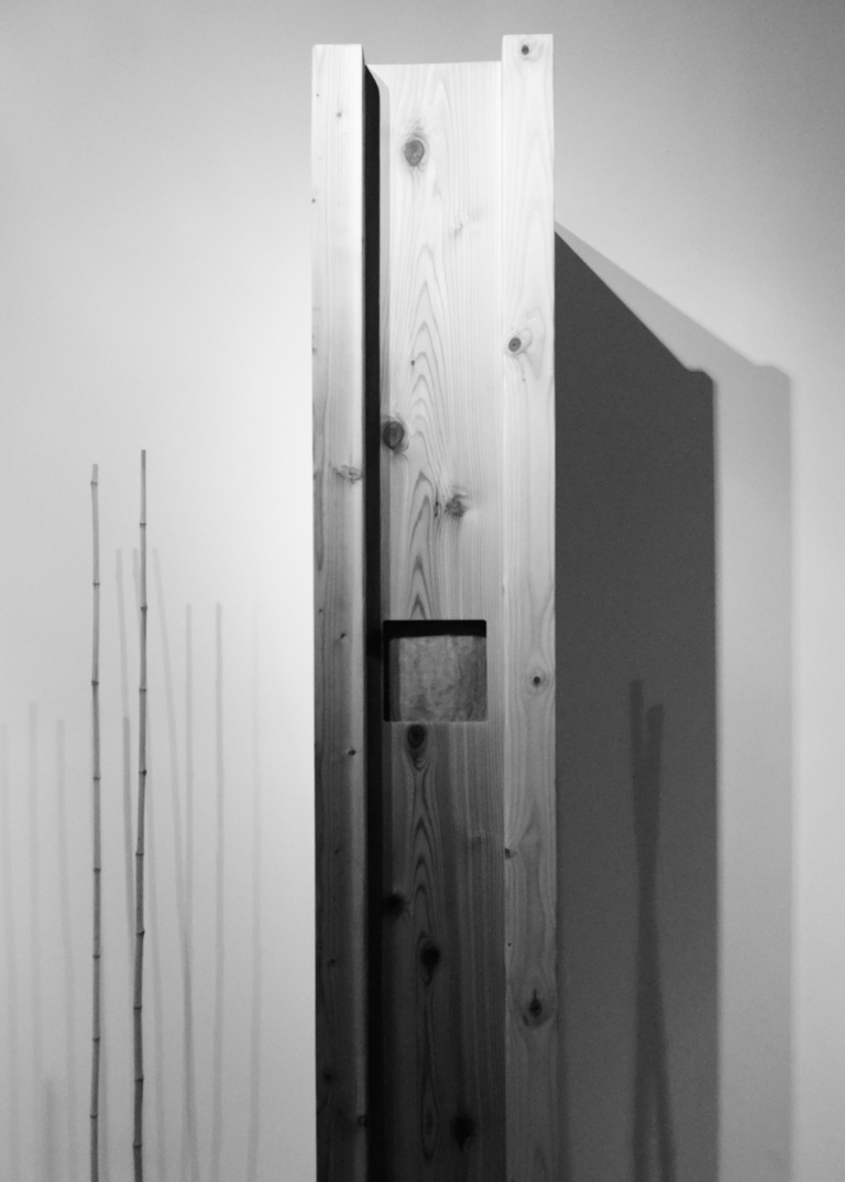 """Circulatory 96"""" x 17"""" x 24"""", cedar, drywall, audio amplification, steel screen, 2014. installation view: I Am Logan Square Gallery, Chicago IL Photography by Jessica Pierotti  Each cedar column contains the captured audio of the artists' heartbeats in this residual piece of  Circulatory , 2012 at the Chicago Cultural Center. Installed amongst Austin Knierim 's  LinearHierarchyof theHippocampus : a bamboo grove springing from the hardwood floors of the gallery, visitors experience the heart resonating from the pillars. Pinard stethoscopes, metal cones used by physicians and midwives to listen to heart rhythms, were also available, enabling visitors to listen to each others' pulse."""
