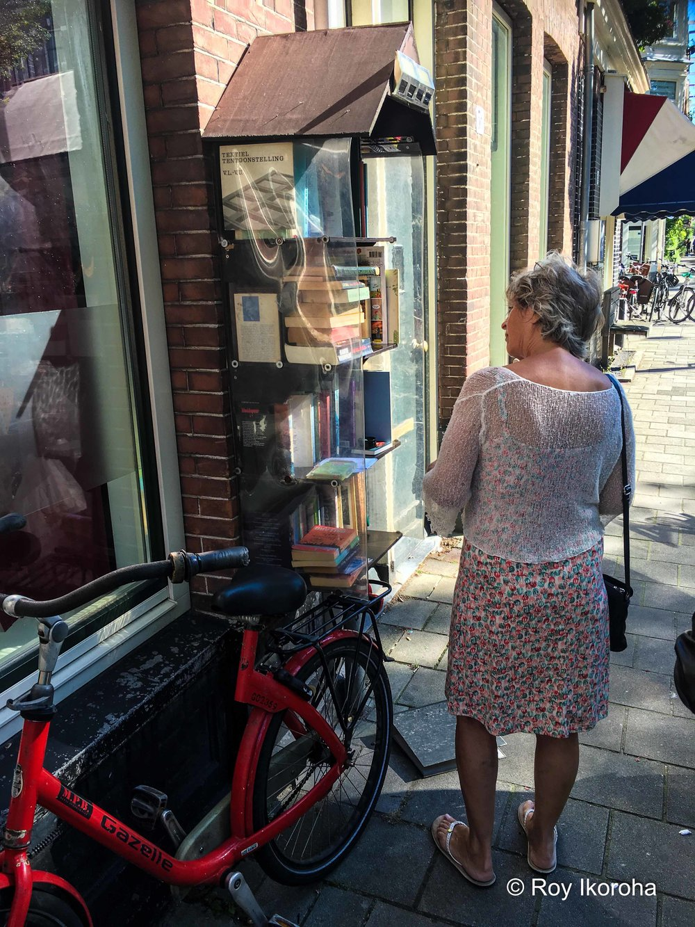 Passer-by deciding on what book to pick up at open street bookcase | Bosboom Toussaintstraat, Amsterdam, Netherlands