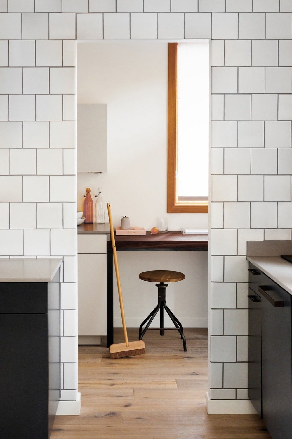 one-wall-of-the-kitchen-is-entirely-clad-in-heath-ceramics-tile-with-a-highly-irregular-glaze.jpg