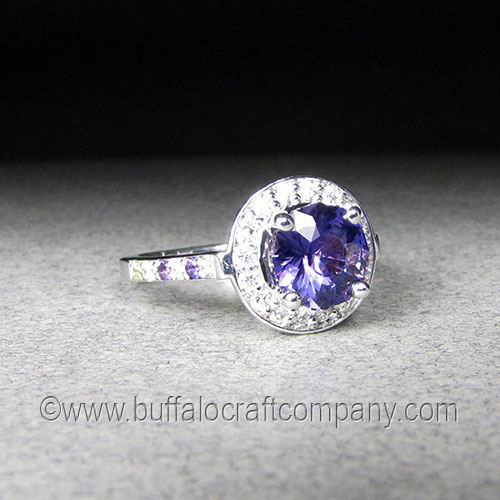"""""""Massey"""" 14k white gold women's haloengagement ring This14k white gold hand fabricatedhalo ring holdsa1.50 ctround purple sapphire surrounded by16 1.5mm VS G color diamonds. The ring shank includes3 diamonds,2 amethyst, and aperidot on either side."""
