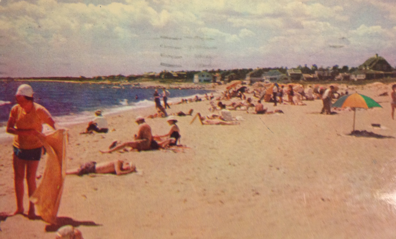 """""""This is the end of the road we are on. Having fun watching the kids in the afternoons. You won't find us in the picture. Doing out best at resting. Irene & Martha"""" A Sunny Day on the beach at Harwichport on Cape Cod, Mass - Sept Sept. 4th 1958"""