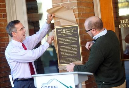 Anthony Edwards / Staff Photo Steve Costello, left, co-organizer of the Gift-of-Life Marathon, and Eric Mallette of the Paramount Theatre unveil a plaque honoring the theater's contributions to the annual 12-day blood drive, which starts Dec. 1.