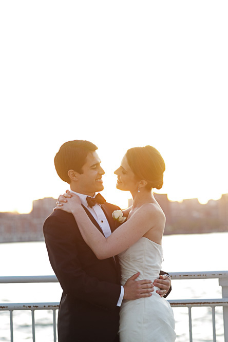 A couple share a moment together in a scene overlooking the Hudson River during their wedding at the Lighthouse at Chelsea Piers.