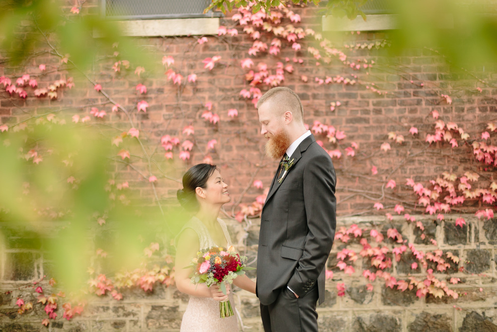 A couple share a moment in front of a colorful brick wall with popping floral colors.