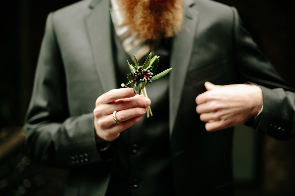 A closeup of a floral detail as a groom pins his boutonniere to his suit.
