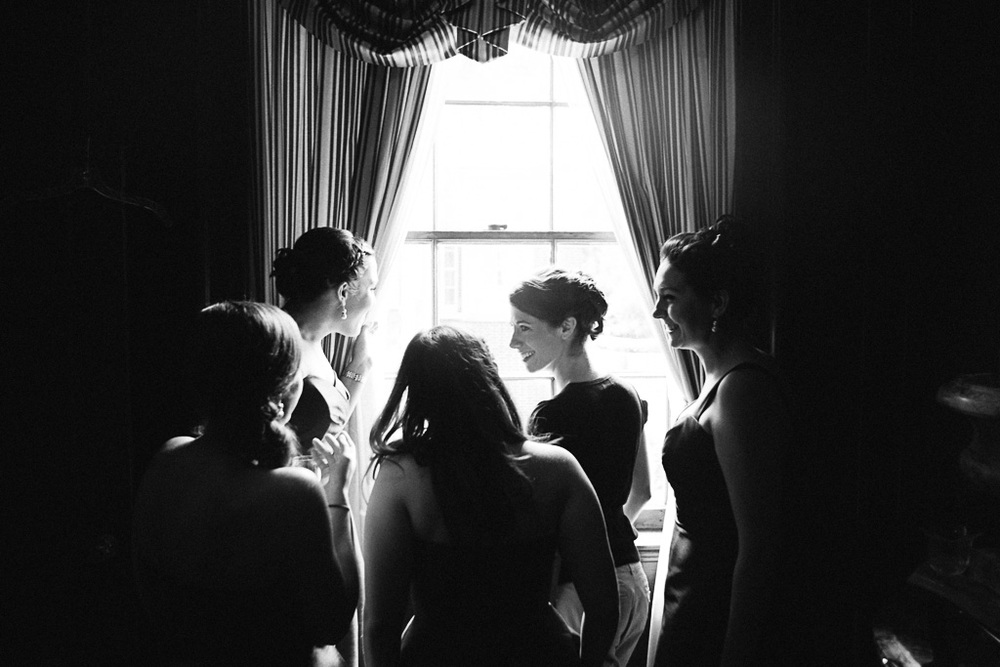 A woman stands in front of a window as her friends help her prepare for the wedding.