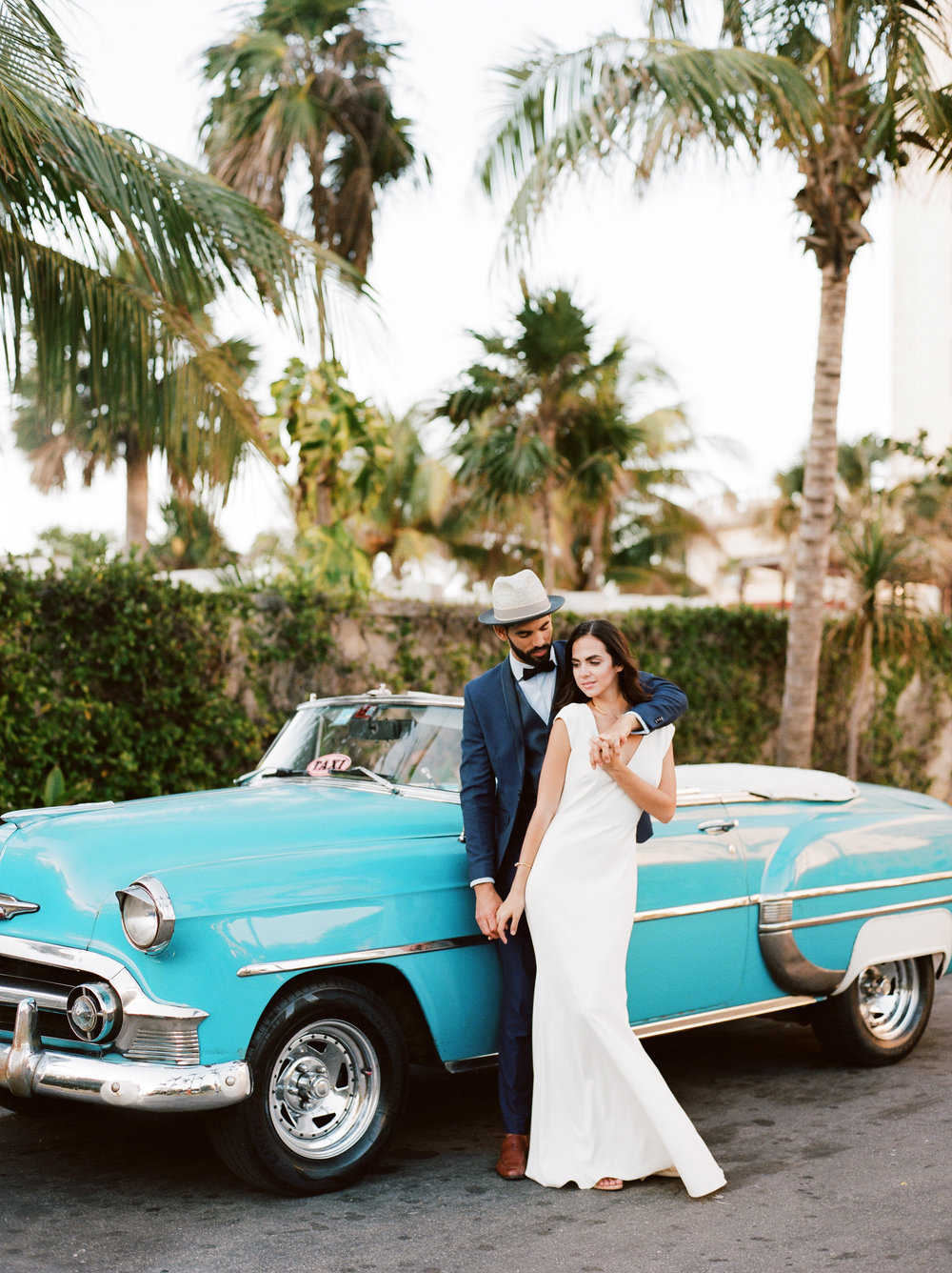 Future Bride and groom by blue vintage chevy in Havana