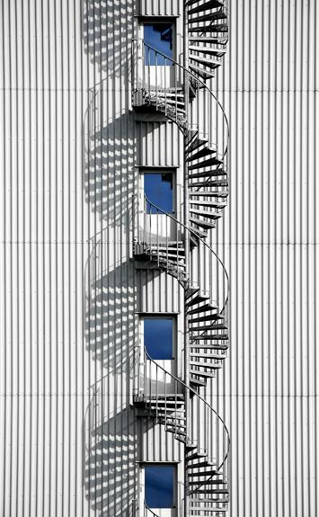 Spiraltrappa där solen skapat ett tjusigt DNA-mönster.