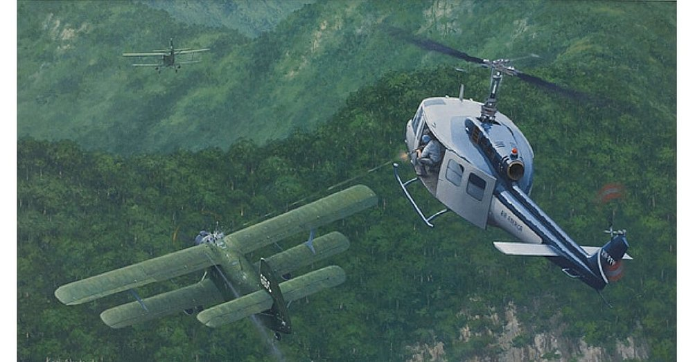 Painting of an Air America Bell 205 helicopter engaging two Vietnam People's Air Force Antonov An-2 biplanes dropping 120 mm mortar rounds on Lima Site 85, Laos,12 January 1968.