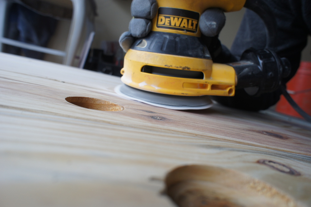 After the resin dries, we sand the material that protrudes from the surface of the top to ensure a flush finished surface.