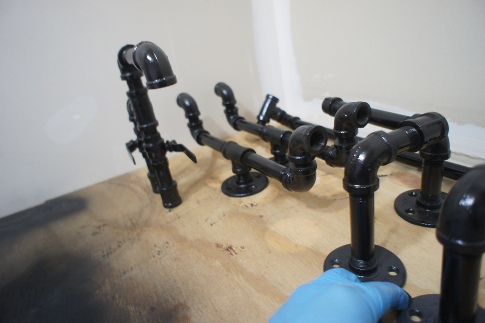 The black pipe hardware receives a second coat of paint to finalize finishing before installation.