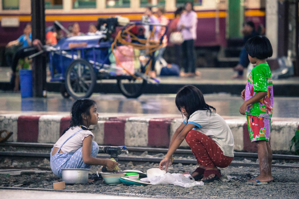 Local kids playing a cooking game on the rail tracks at the central train station in Bangkok.
