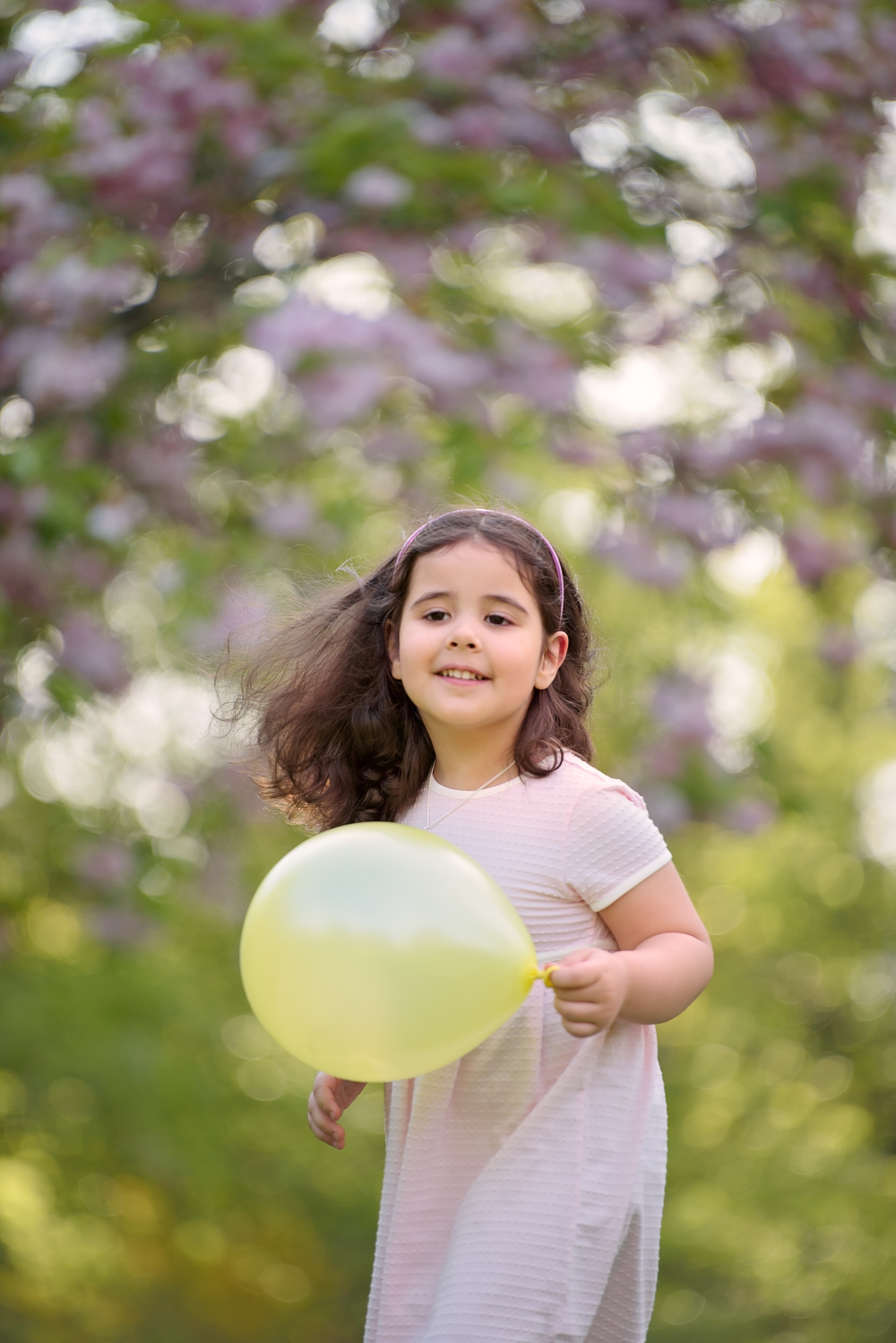 Girl photographed with balloon in pink cherry blossoms, Kensington Gardens