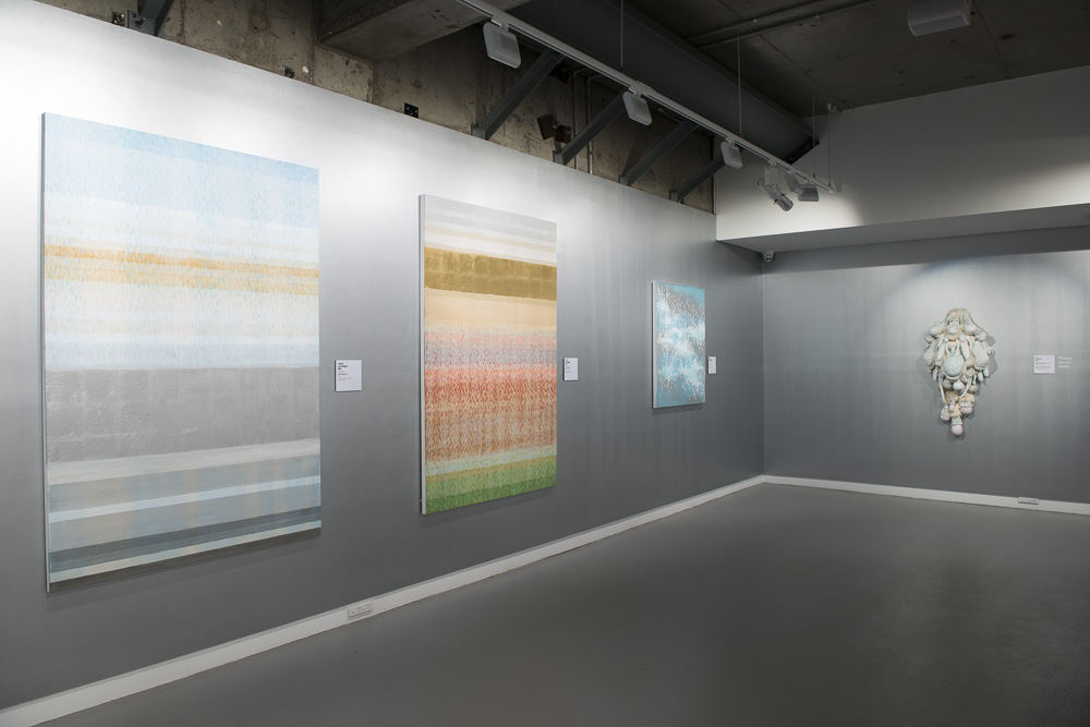 "Installation shots of my paintings in ""Imagine"" on a silver wall! Color Bands #2, 2014. Acrylic and Alum-Silver on Canvas. 72""x48"" (182.8x121.9cm)  Color Bands #3, 2014. Acrylic and Alum-Silver on Canvas. 72""x48"" (182.8x121.9cm) Sway, 2011. Acrylic and Alum-Silver on Canvas. 42""x35"" (107x89cm)"