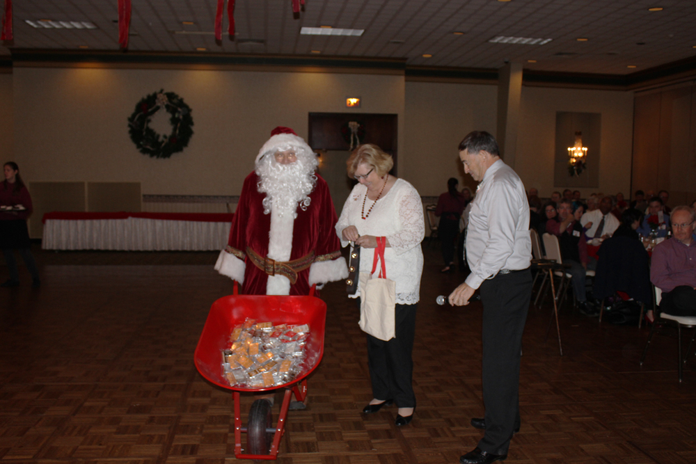 From left to Right: Santa, Beverly Hess, and Andrew Muller, Jr pictured as Santa   surprised all of the RBMN employees with a gift of a 10 ounce bar of silver