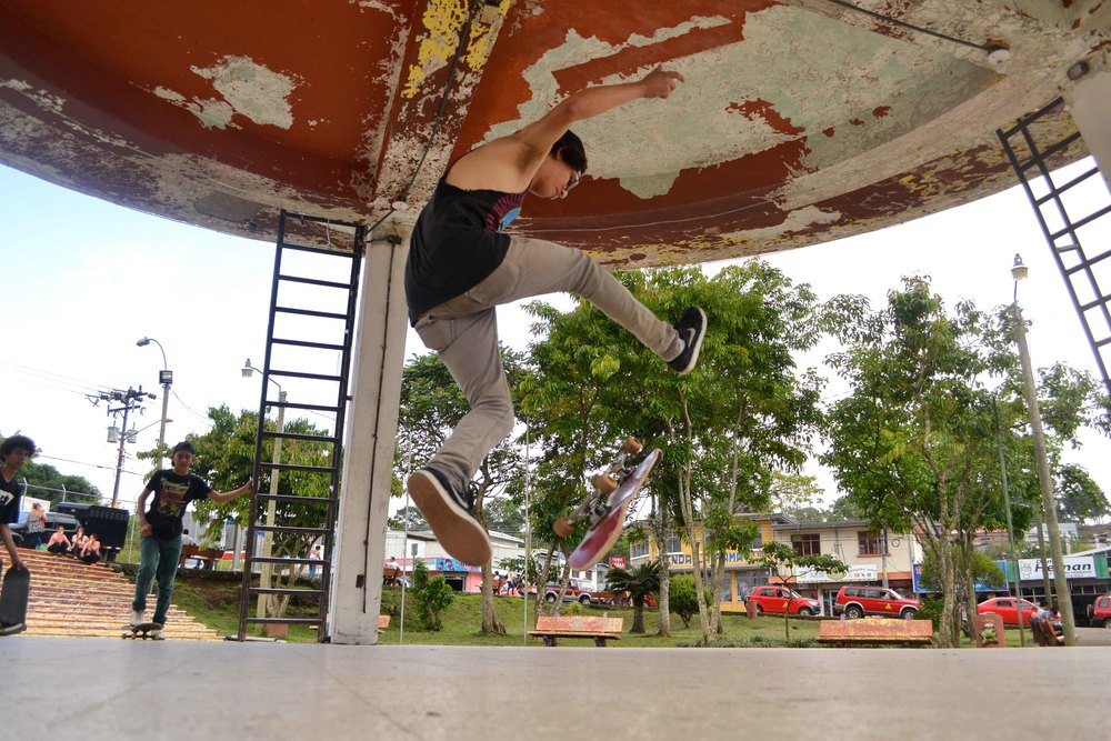 Monopatinador: A skateboarder tricks in Puriscal's central park