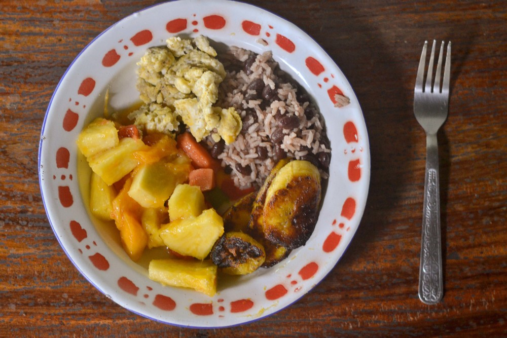 A typical breakfast: fresh mixed fruit, scrambled eggs, gallo pinto (rice and red beans mixed together), and fried plantains.