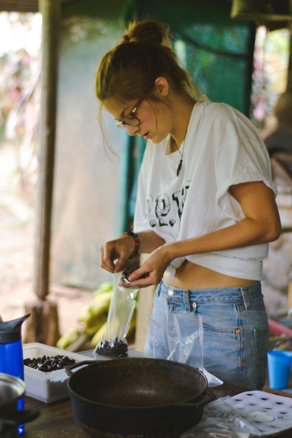 Amie puts toasted and peeled cacao beans into bags to sell
