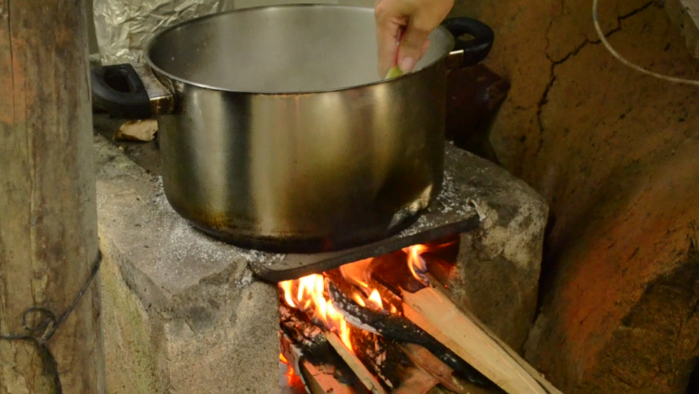 Mariana cooks rice pudding on the outdoor wood-powered stove.  Cooking it over the fire gives it a richer taste, as the smoke intertwines with the flavors of the pudding.