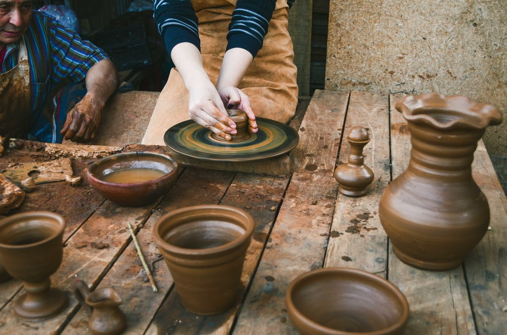A student tries her hand at pottery under the watch of the artisanal potter in Buín