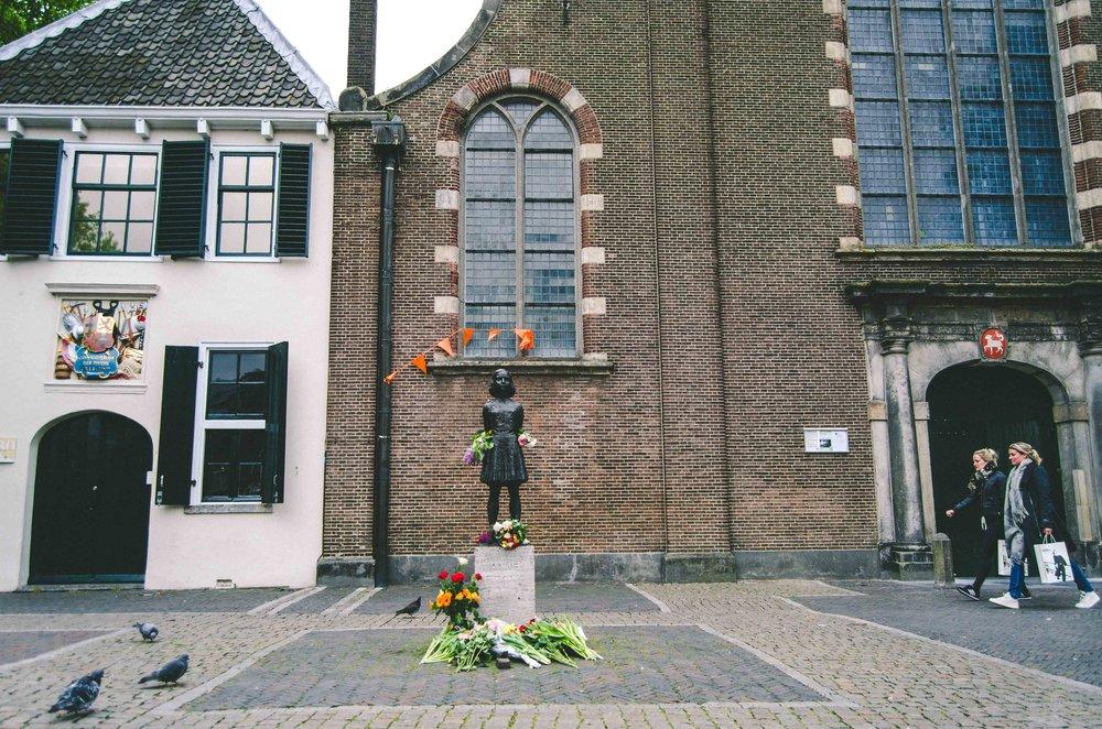 Anne Frank memorial statue on her birthday + orange flags in honor of King's Day ( Koningsdag )