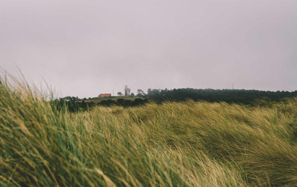 The island lighthouse amidst morning fog.