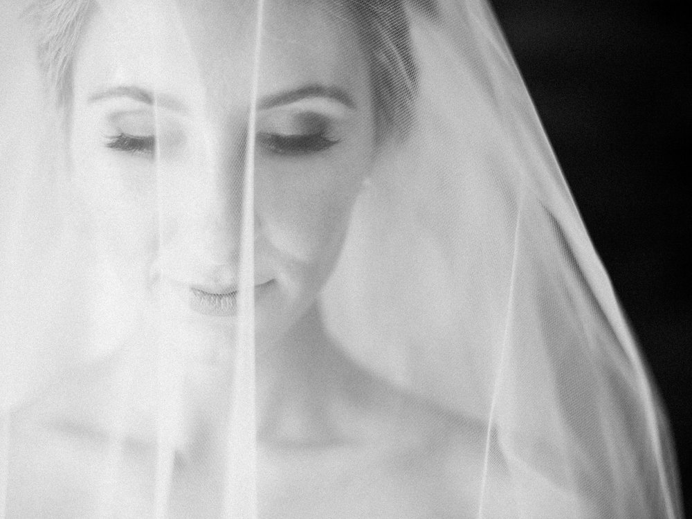 Black and white portrait of a bride in her veil getting ready