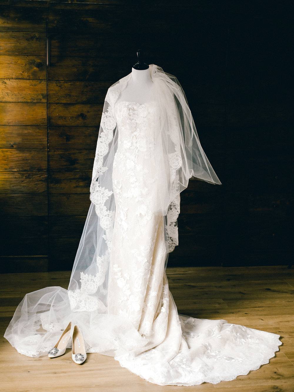 A wedding dress on a bust with a veil and shoes