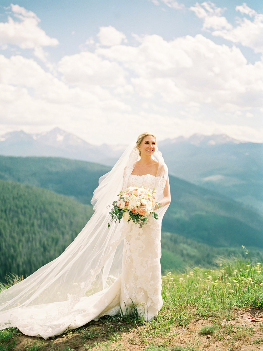 Bride with her veil and bouquet on top of a mountain in Vail