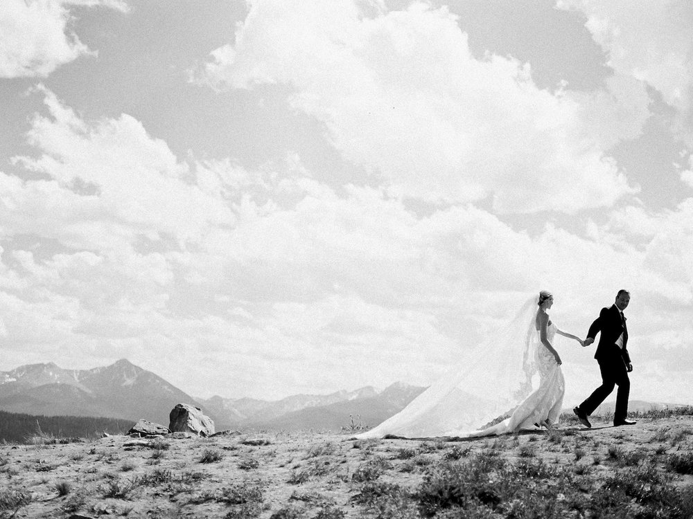 Black and white portrait of a bride and groom on top of a mountain