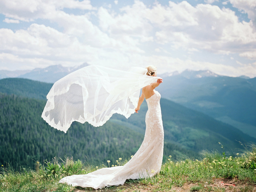 A bride with her veil in a gust of wind on a mountain top in Vail