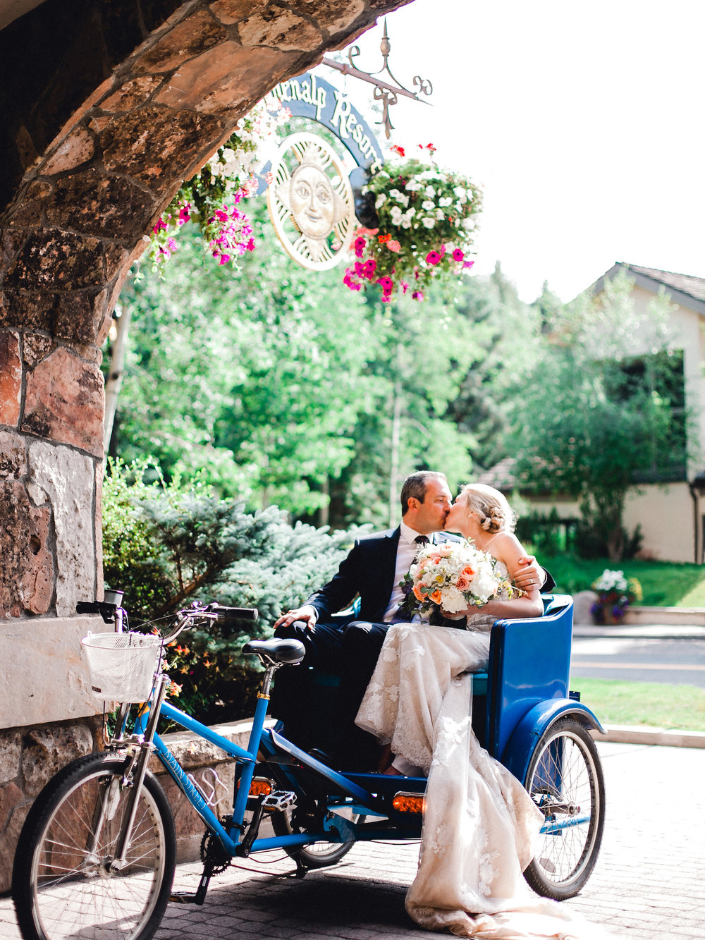 Bride and Groom arriving for their wedding reception at the Sonnenalp in a pedicab