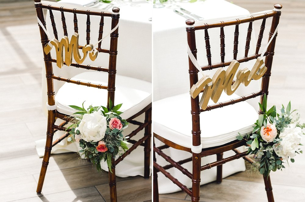 chiavari chairs with mr and mrs signs and flowers for a wedding reception