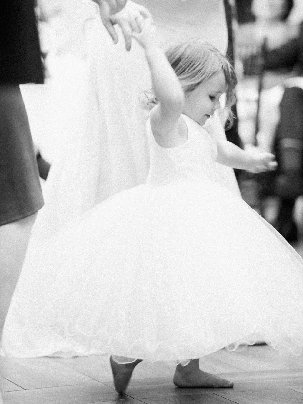 Flower girl twirling in a tutu at a wedding