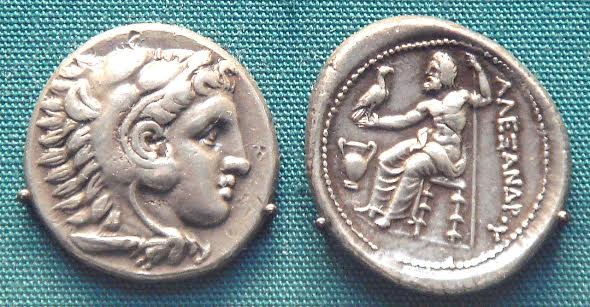 Either a silver coin of Alexander the Great wearing the lion skin of Herakles (Hercules), considered one of his ancestors, or Herakles himself in a coin struck in Alexander's time. British Museum.