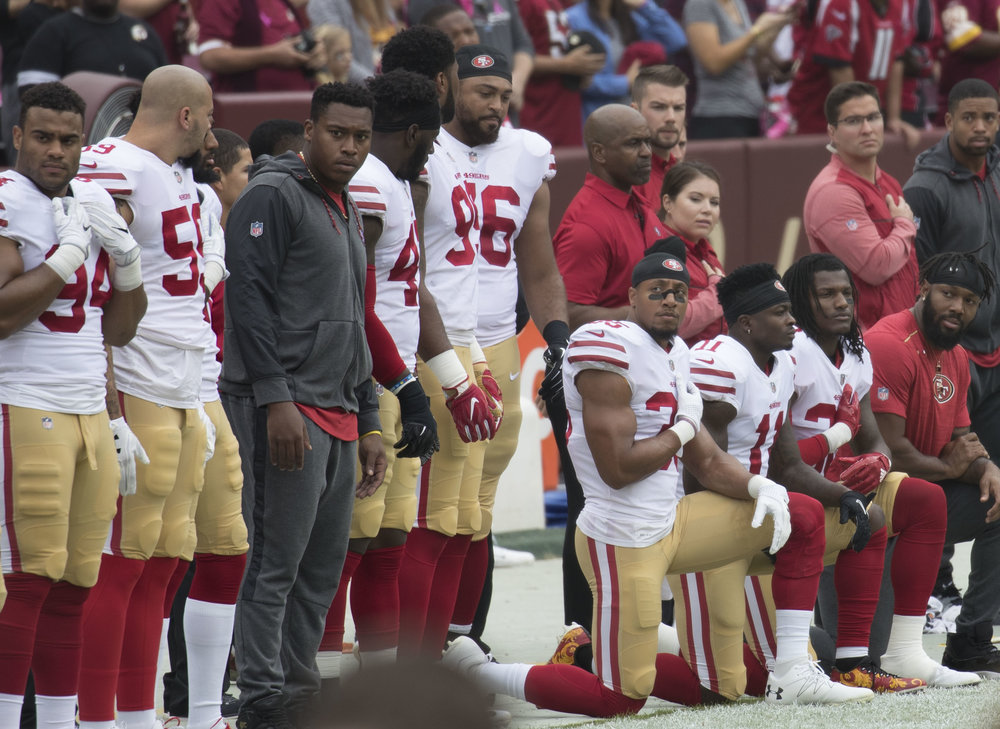 "Some members of the San Francisco 49ers kneeling during ""The Star-Spangled Banner"" before a game against the Washington Redskins at FedEx Field in Landover, Maryland on Oct. 15, 2017. Photograph by Keith Allison."