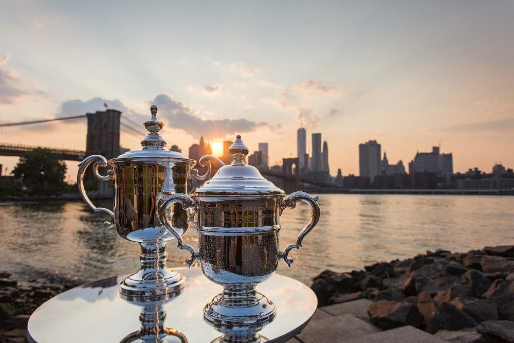 The trophies from the US Open's men's and women's singles championships gleam against the backdrop of the Brooklyn Bridge and Lower Manhattan. Tim Camuso/USTA