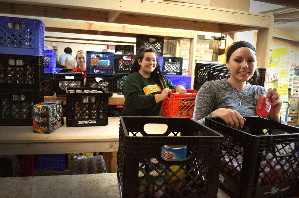 Shaela, Mariah, and Kelsey organizing food in the food pantry