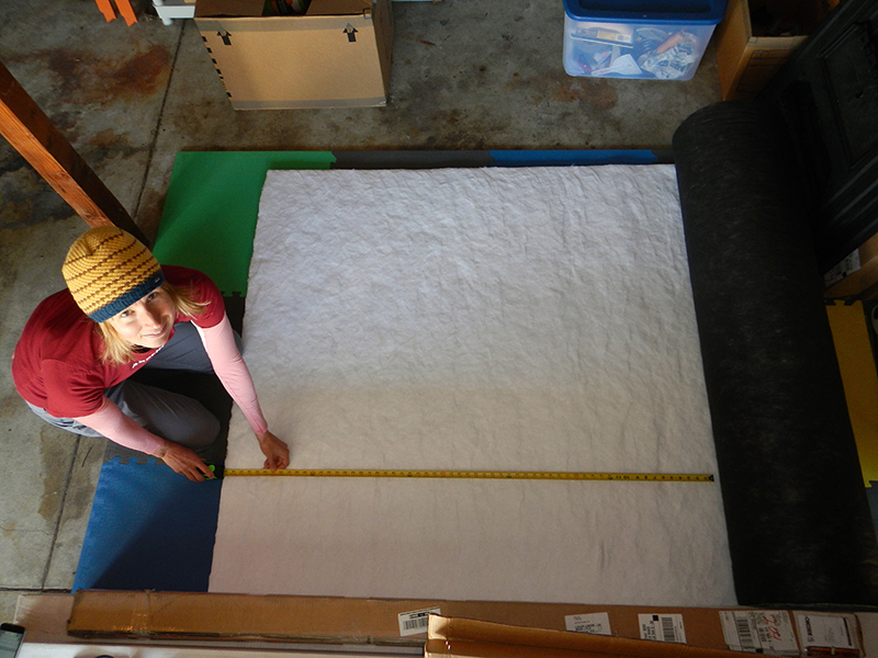 "Andrea measuring a long panel of insulation. The roll is 60"" wide."