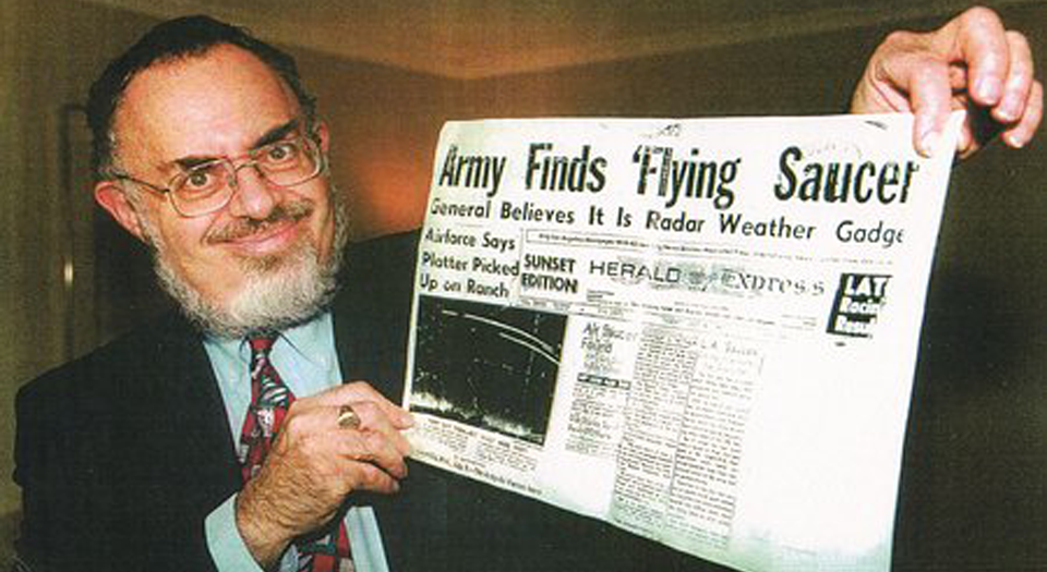 Mr. Friedman holding up  a photocopy of the Los Angeles Herald-Express from July 8, 1947 - part of his Roswell memorabilia collection. (     © Stanton Friedman)